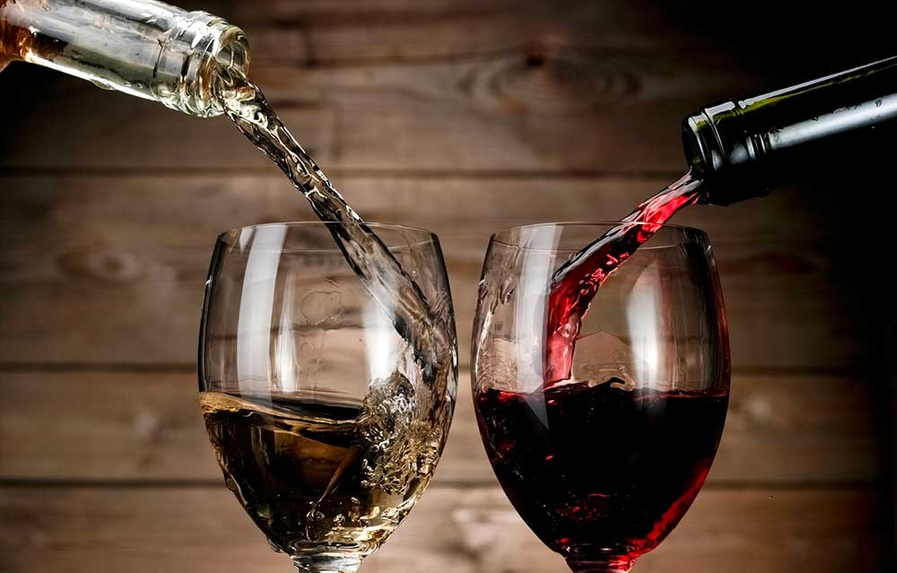 Re and white wine pouring on wood background